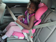 kid in car seat in pink