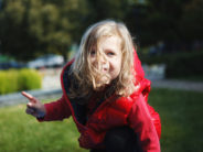 Adorable little child, blonde toddler girl in a red jacket, playing in the autumn Park on the Playground