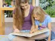 Babysitter schaut Buch mit kleinem Mädchen