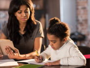 Mother looking at cute little daughter doing homework at home, homework help concept