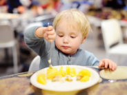 Cute toddler boy eating potatoes in indoors cafe