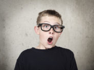 Surprised boy with black glasses