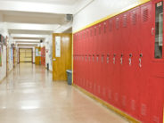 An empty highschool hallway with red lockers on the right side