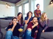A group of friends eating pizza wathing tv sitting on the couch in the room.