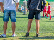 Fathers watching their sons playing soccer game, kids playing football, selective focus