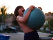 unsplash boy playing with big blue ball