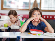 Bored schoolboy looking away while sitting at desk with girl in background at classroom