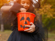 Crop happy girl in witch costume taking sweet from bucket while trick or treating in autumn park during Halloween celebration