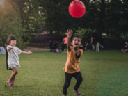 unsplash children playing with big red ball